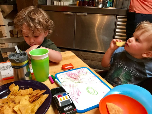 Two little boys eating in a restaurant