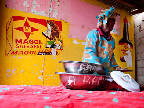 African woman cooking in front of a Maggi cube sign