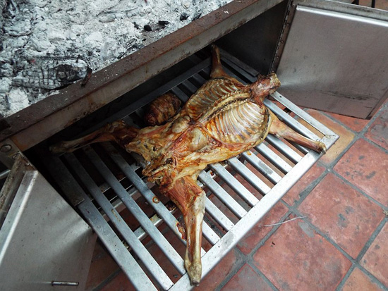 Cabrito, or goat, coming out of the caja china roasting box in Monterrey, Mexico.