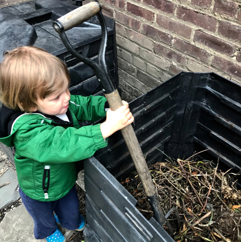 Child with a compost bin in a backyard in Queens