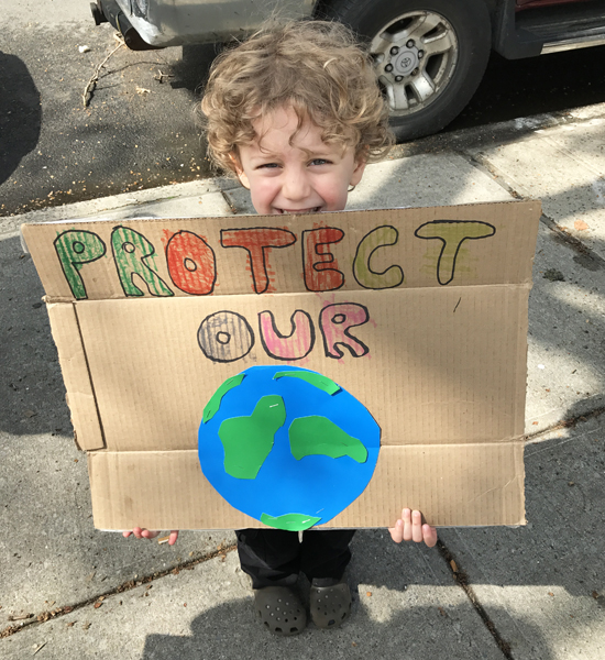 Child holding a Protect the Earth sign for Earth Day