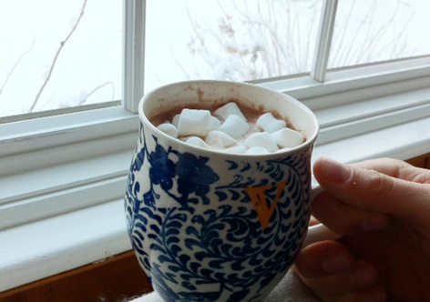 Hot chocolate with marshmallows in winter, before a snowy background