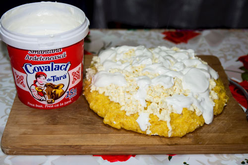 Homemade Romanian mamaliga with cheese and sour cream ready to eat, with a container of sour grain.