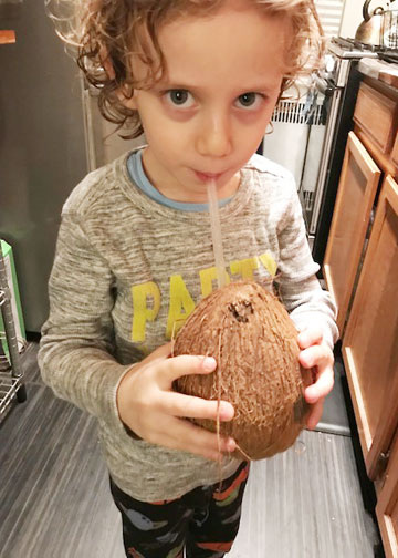 Young boy drinking coconut water from the coconut in a kitchen.