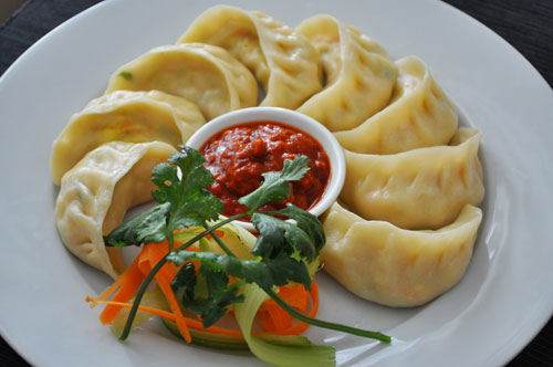 Momo dumplings surrounding a pot of chili sauce in Tibet