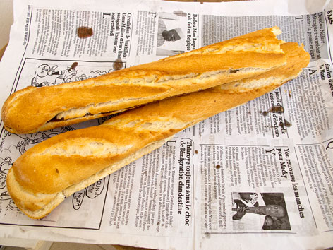 Two breakfast baguettes on newspaper in Dakar, Senegal.