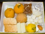 A box of Indian sweets including burfi, milk cake, and peda from Anupama in Delhi, India.